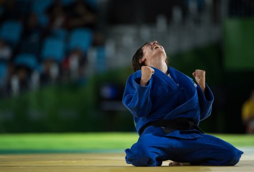 Sandrine Martinet of France kneels on the mat with her fists clenched after winning gold at the Rio 2016 Paralympics