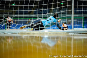 Chunhua Wang of China's women's goalball team spread herself across the front of goal