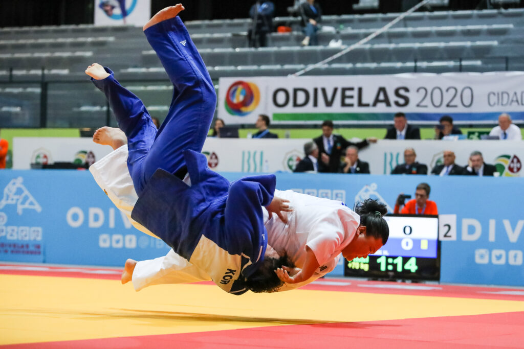 Hongyu Wang and an opponent are pictured as if they are hovering in the air during a throw