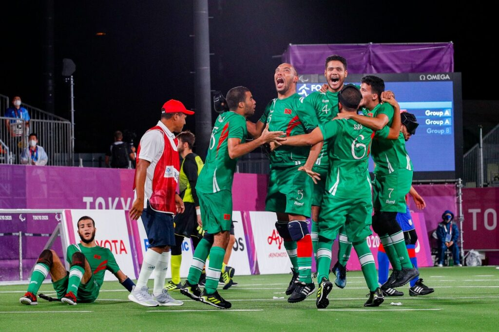 Players and coaches from the Moroccan blind football team jump up and down after claiming a semi-final place at the Tokyo 2020 Paralympic Games