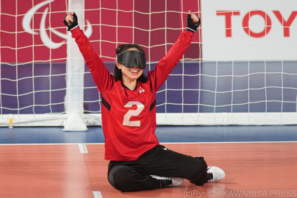 A female goalball player from Japan sits in goal and raises her arms in the air with delight