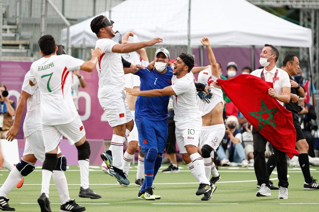 Moroccan blind football players jump high into the air as their team staff run onto the pitch with their national flags during the blind football bronze medal match at Tokyo 2020
