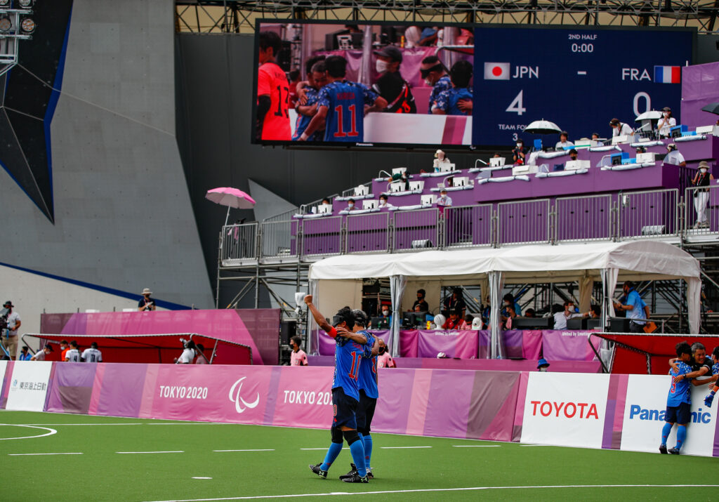 Two Japanese players embrace as a wide shot of the blind football venue is shown