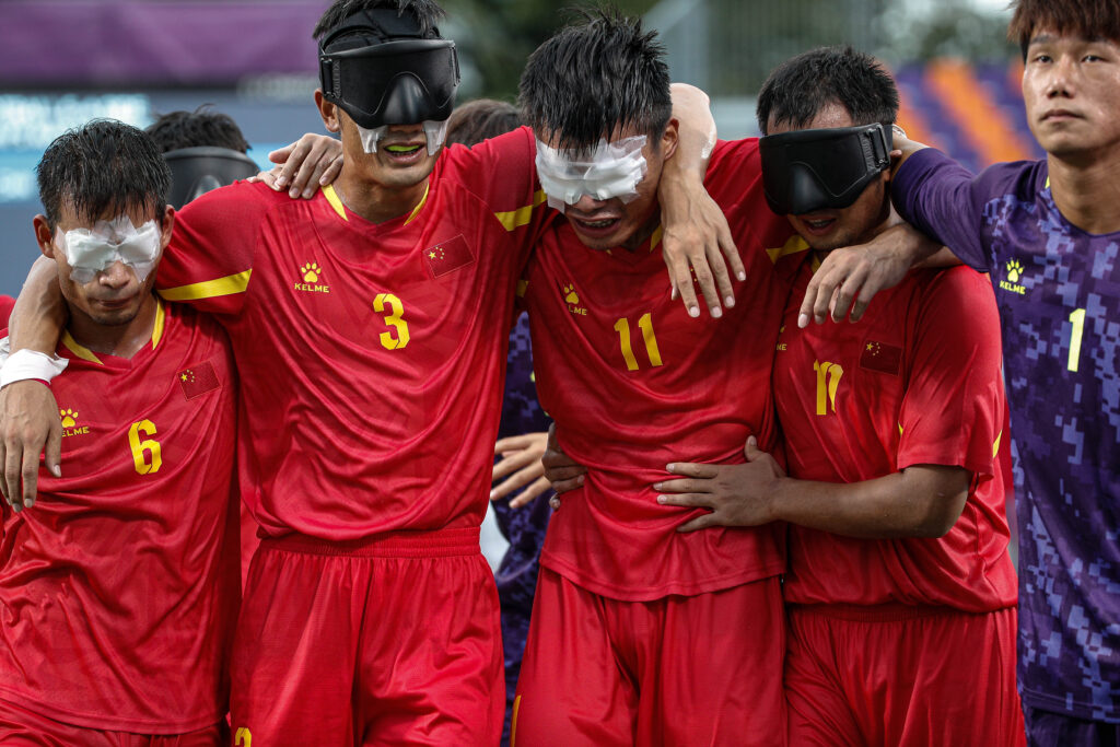 Chinese blind football players link arms and embrace