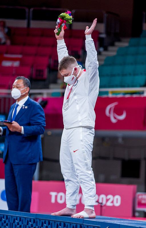Benjamin Goodrich holds his hands in the air after receiving his silver medal at Tokyo 2020