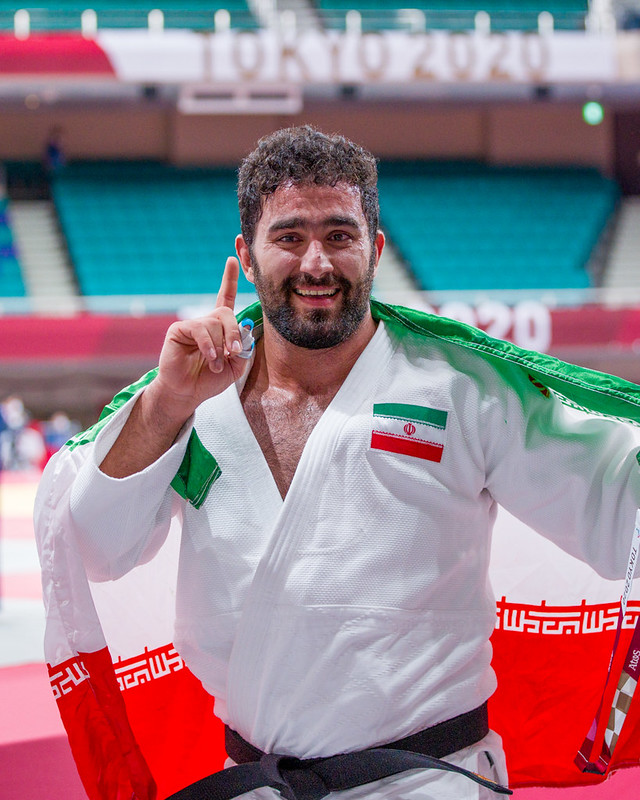 Mohammed Kheriollahzadeh makes a No.1 symbol with his finger whilst holding the flag behind his shoulder
