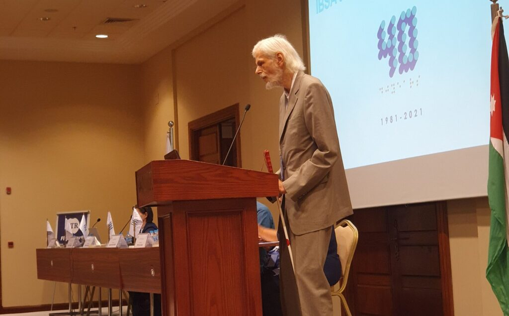 Jens Bromann of Denmark stands and speaks on the podium at the 2021 IBSA General Assembly